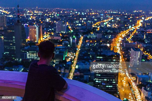 High Angle View Of Man Standing On Building Terrace Against Illuminated City At Dusk