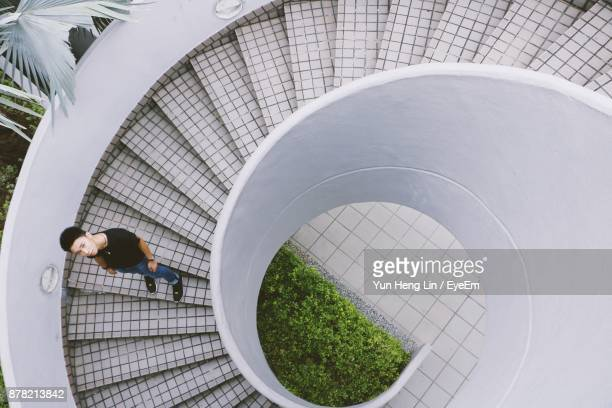 High Angle View Of Man Standing On Spiral Staircase