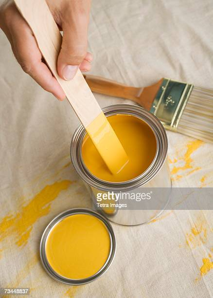 High angle view of man stirring paint in paint can