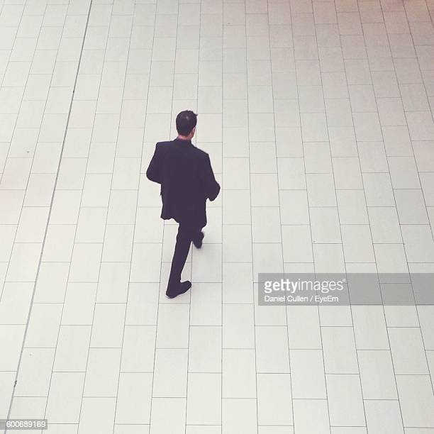 High Angle View Of Man Walking In Pavement