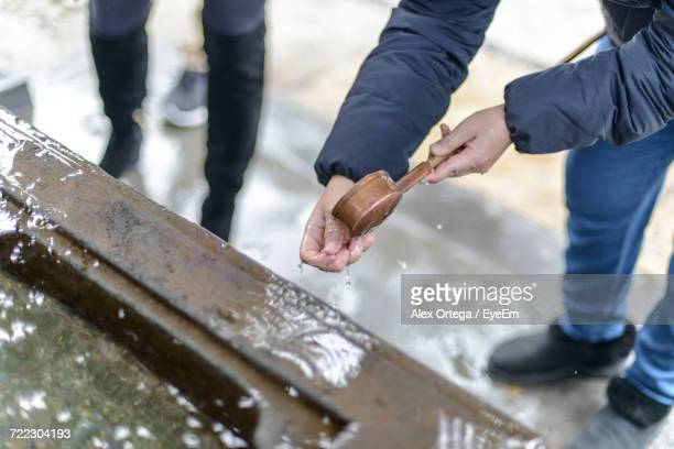 High Angle View Of Man Washing Hands With Holy Water At Temple