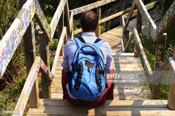 High Angle View Of Man With Backpack Sitting On Wooden Steps