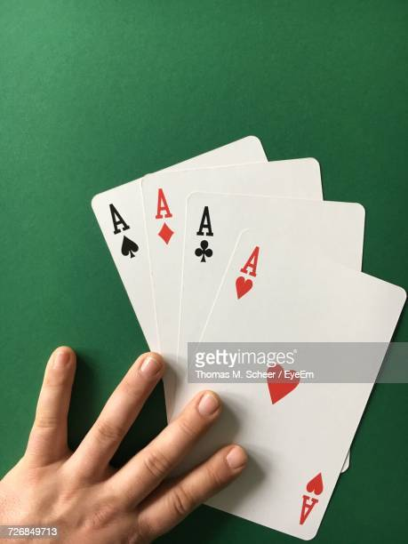High Angle View Of Man With Three Aces Cards On Green Table