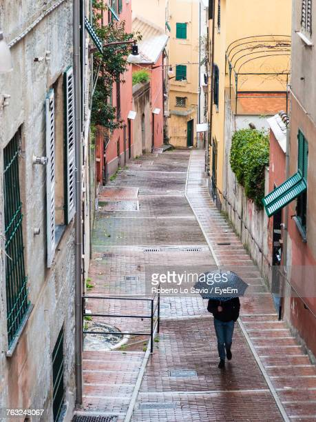 High Angle View Of Man With Umbrella Walking On Alley Amidst Buildings