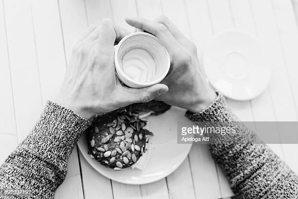 High angle view of mans hands holding coffee cup at cafe table