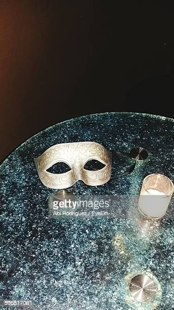 High Angle View Of Masquerade Mask With Illuminated Candle On Table