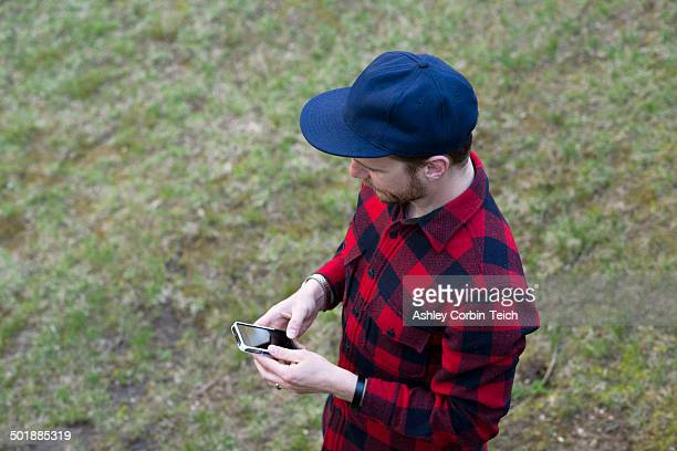 High angle view of mid adult man texting on smartphone