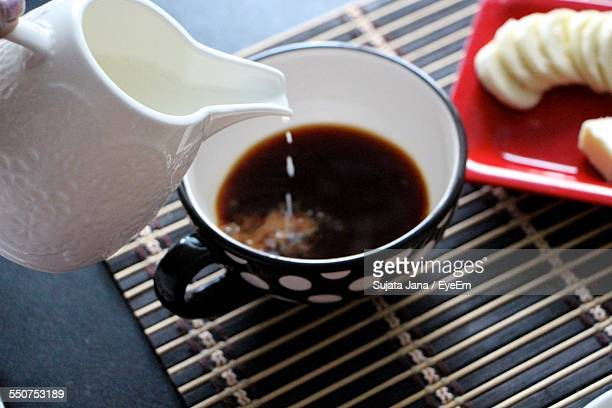 High Angle View Of Milk Pouring Into Tea Cup
