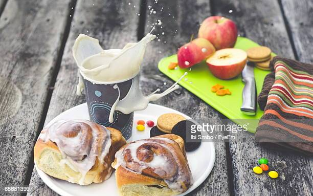 High Angle View Of Milk Splashing By Dessert In Plate On Table