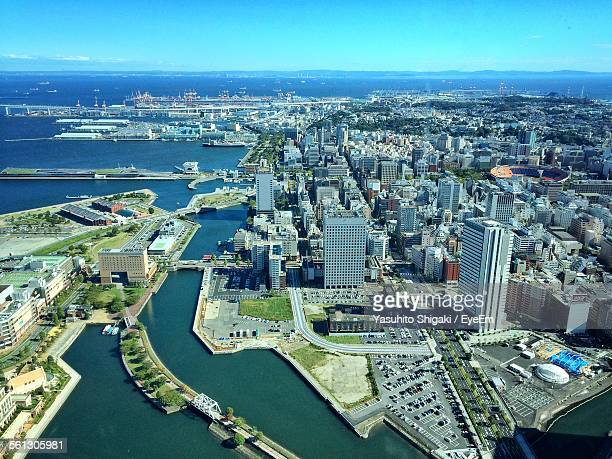 High Angle View Of Modern Buildings And Sea Against Blue Sky In City