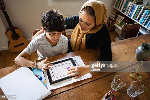 High angle view of mother assisting son in using digital tablet while studying at home