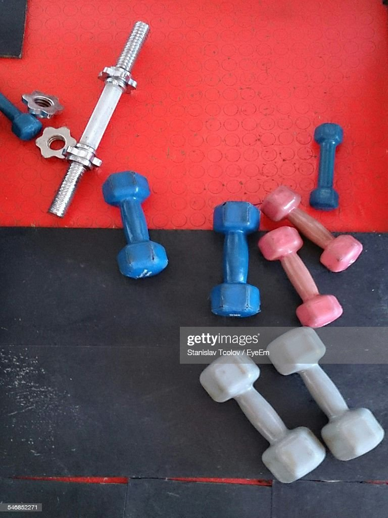 High Angle View Of Multi Colored Dumbbells On Floor At Home