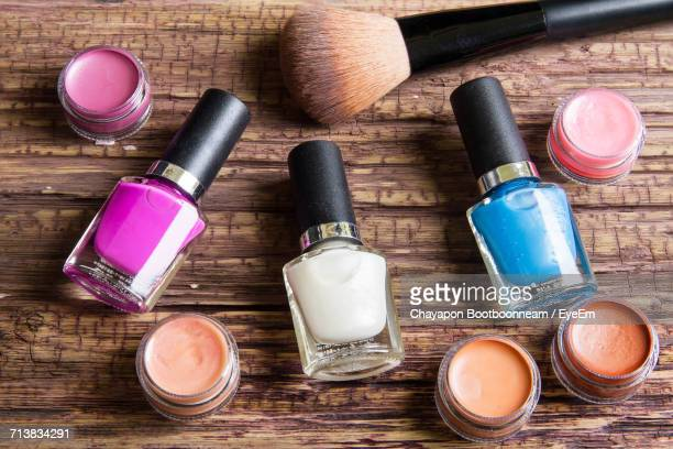 High Angle View Of Nail Polish Bottles With Lip Balm And Make-Up Brush On Wooden Table