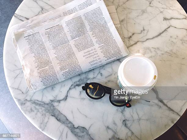 High Angle View Of Newspaper By Sunglasses And Disposable Cup On Table