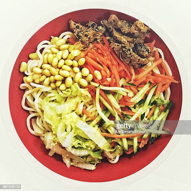 High Angle View Of Noodles With Vegetables In Plate On White Background