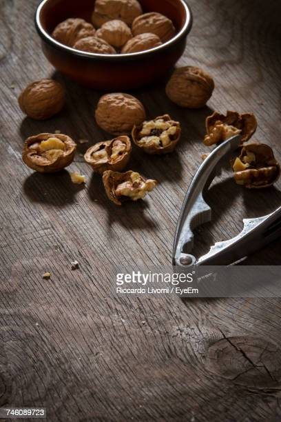 High Angle View Of Nutcracker With Walnuts On Wooden Table