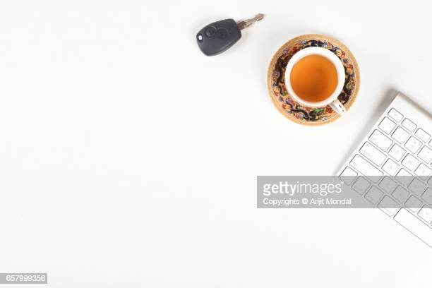 High angle view of office desk table with car key, green tea and computer keyboard, white background copy space
