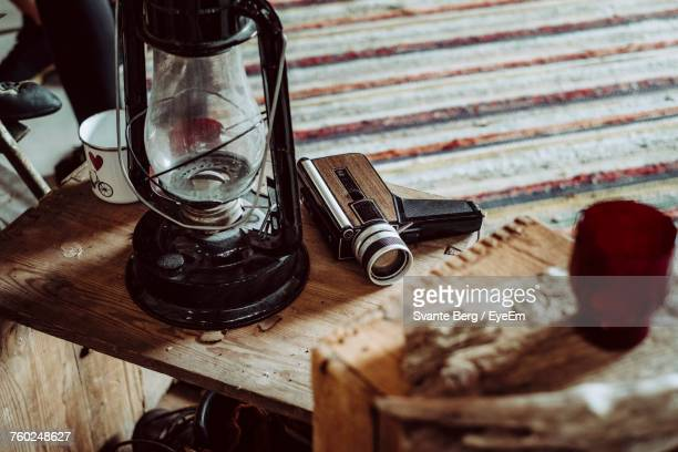 High Angle View Of Oil Lamp And Camera On Wooden Table