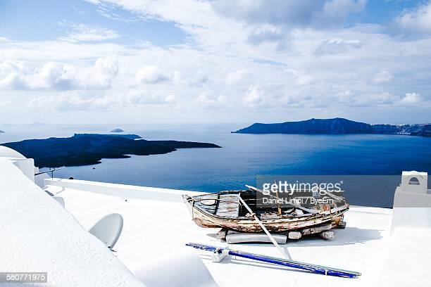High Angle View Of Old Weathered Boat On Building Terrace By Sea Against Cloudy Sky