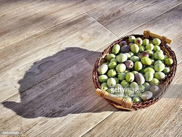 High Angle View Of Olives In Basket On Wooden Table