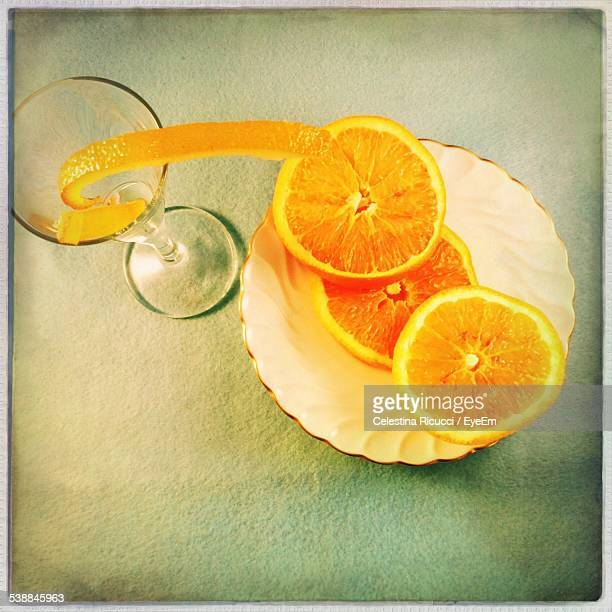 High Angle View Of Orange Slices In Bowl By Martini Glass On Table