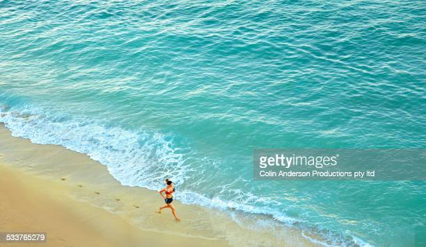 High angle view of Pacific Islander woman running on beach
