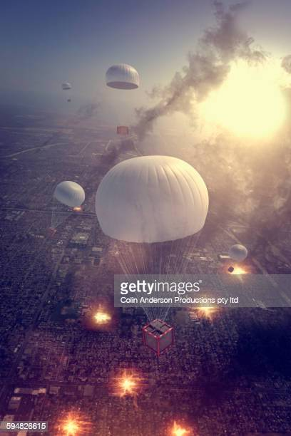 High angle view of packages parachuting over war zone