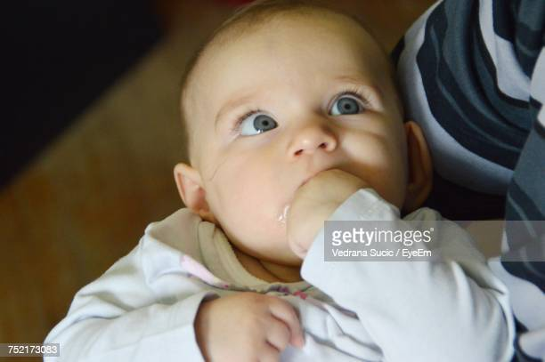 High Angle View Of Parent Holding Baby At Home