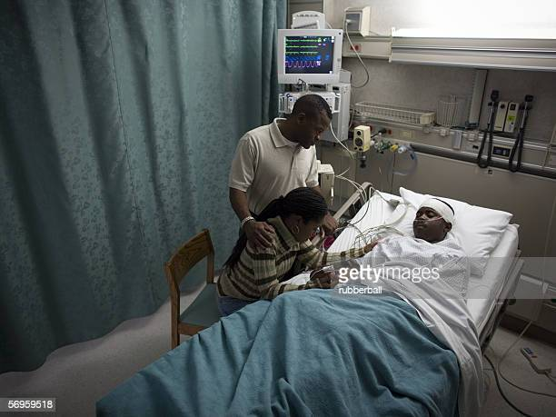 High angle view of parents looking at their teenage son in the hospital