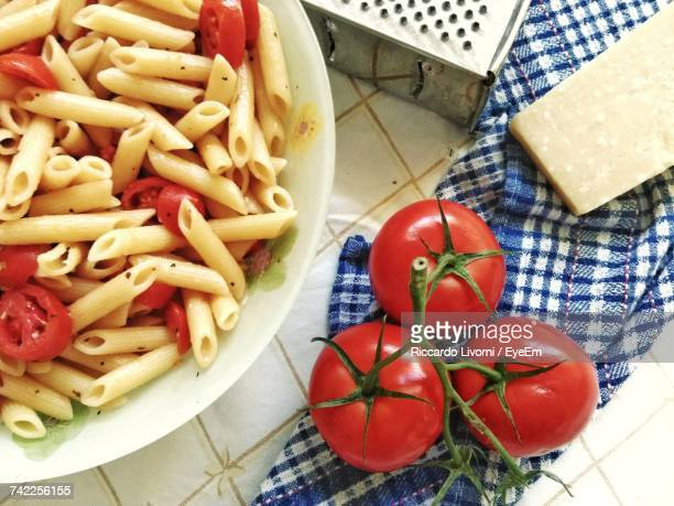 High Angle View Of Pasta By Tomatoes On Table