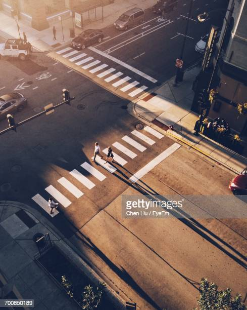High Angle View Of People Crossing Road In City On Sunny Day