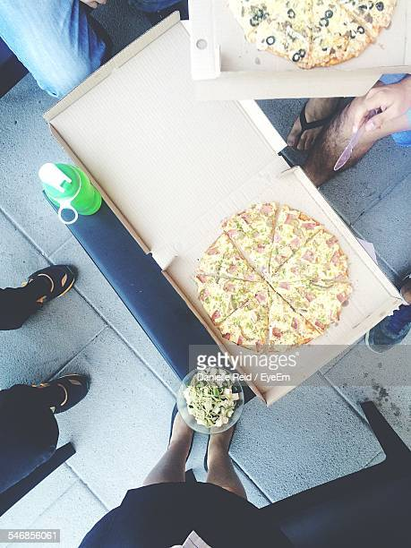 High Angle View Of People Eating Pizzas At Home