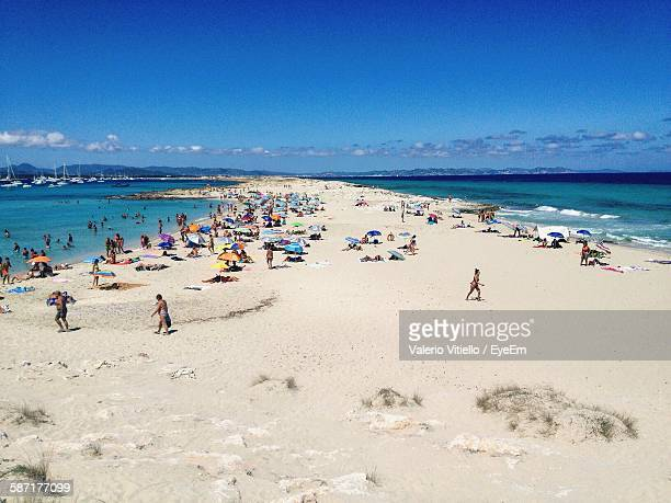 High Angle View Of People Enjoying At Beach Against Blue Sky