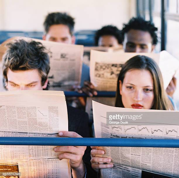 high angle view of people in a commuter vehicle reading the newspaper