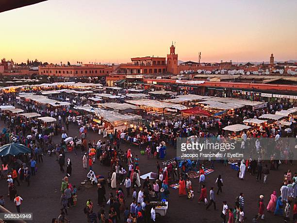 High Angle View Of People In Market Against Sky During Sunset