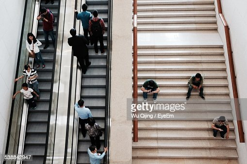 High Angle View Of People On Steps And Escalator In Building
