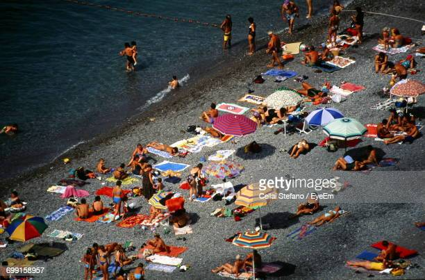 High Angle View Of People Resting By Parasols At Beach