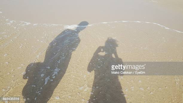 High Angle View Of People Shadow On Shore