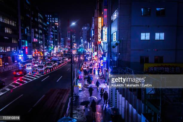 High Angle View Of People Walking On Sidewalk In City At Night