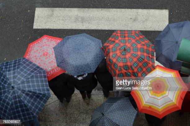 High Angle View Of People With Umbrellas On Road