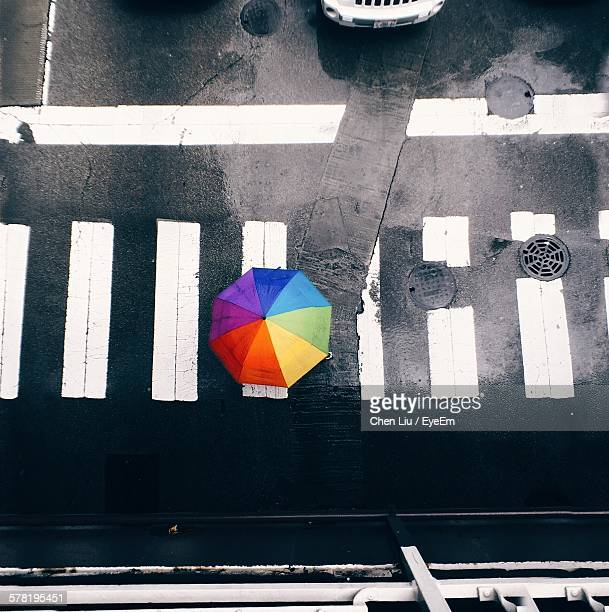 High Angle View Of Person Carrying Umbrella On Zebra Crossing