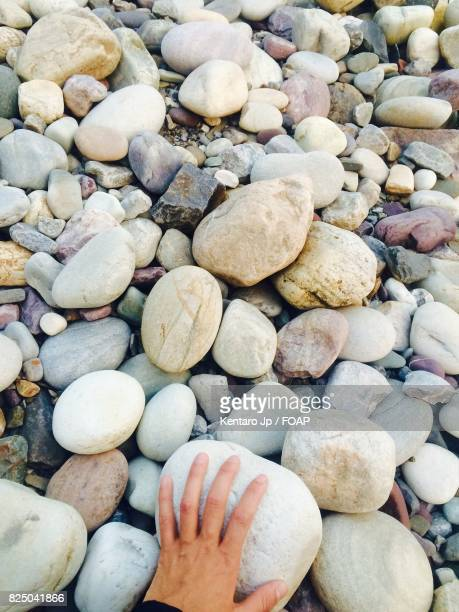 High angle view of person hand on stone