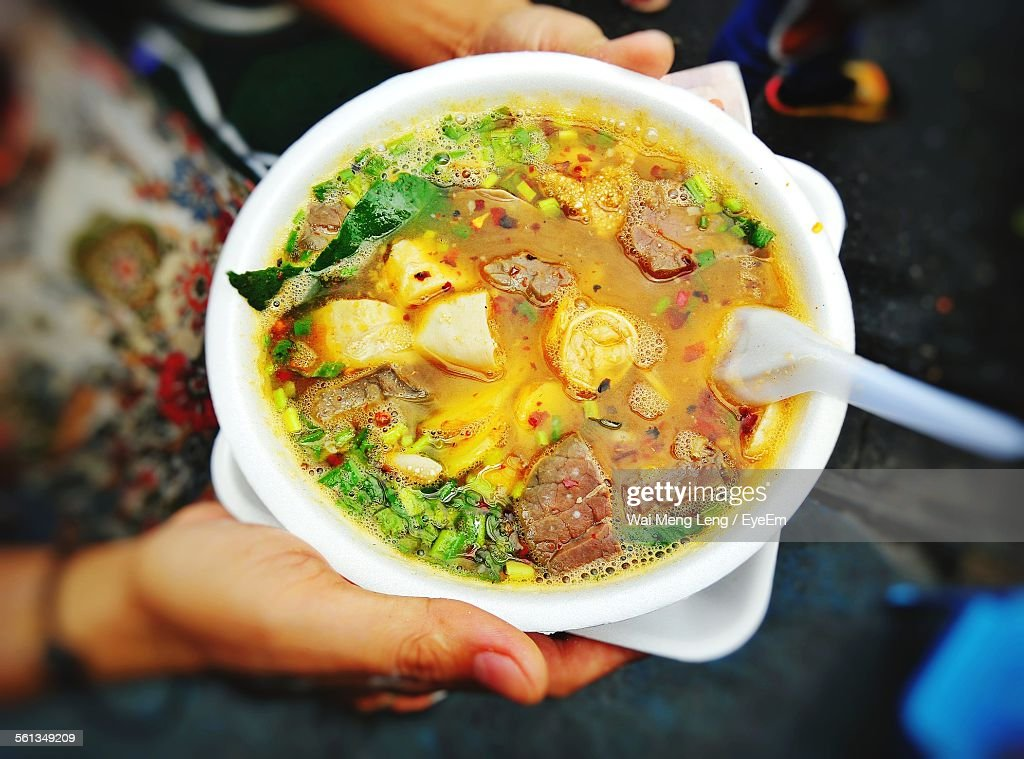 High Angle View Of Person Holding Soup In Bowl