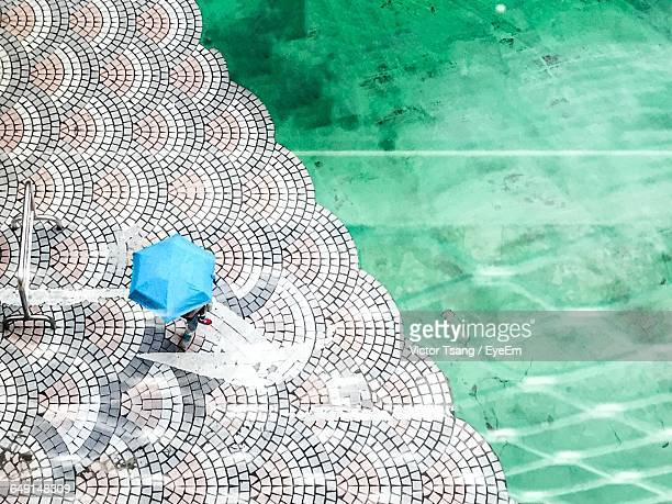 High Angle View Of Person Standing With Blue Umbrella At Poolside