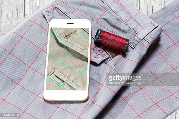 High Angle View Of Picture Displayed On Smart Phone By Spool On Trousers