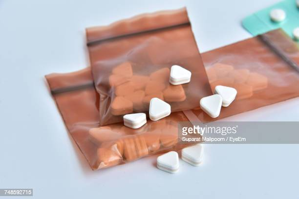 High Angle View Of Pills In Packets On White Background