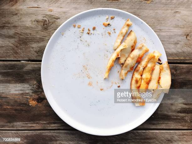 High Angle View Of Pizza Leftovers In Plate On Wooden Table