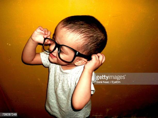 High Angle View Of Playful Boy Wearing Eyeglasses Against Wall
