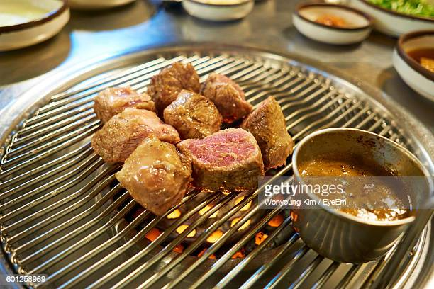 High Angle View Of Pork Meat Cooking On Barbeque At Restaurant