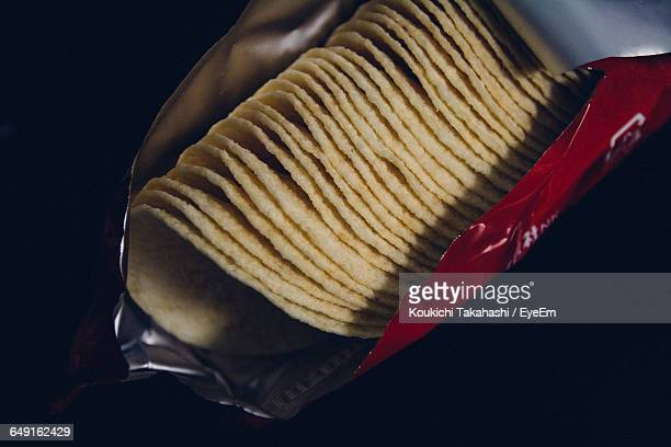 High Angle View Of Potato Chips In Package On Black Background